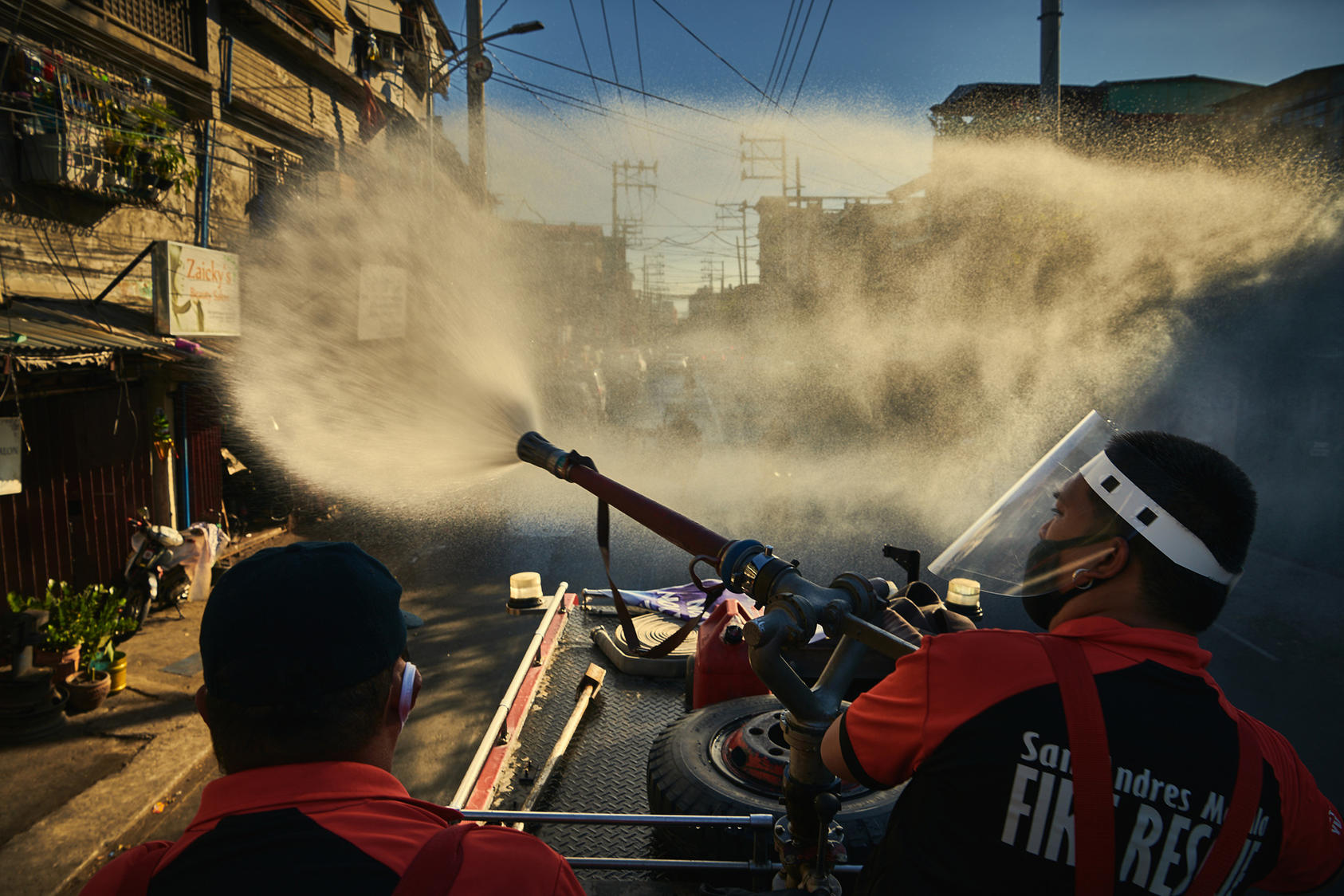 Firefighters spray disinfectant along a road in Manila, Philippines, on April 6, 2020, in an effort to keep the coronavirus from spreading. (Photo by Jes Aznar/New York Times)