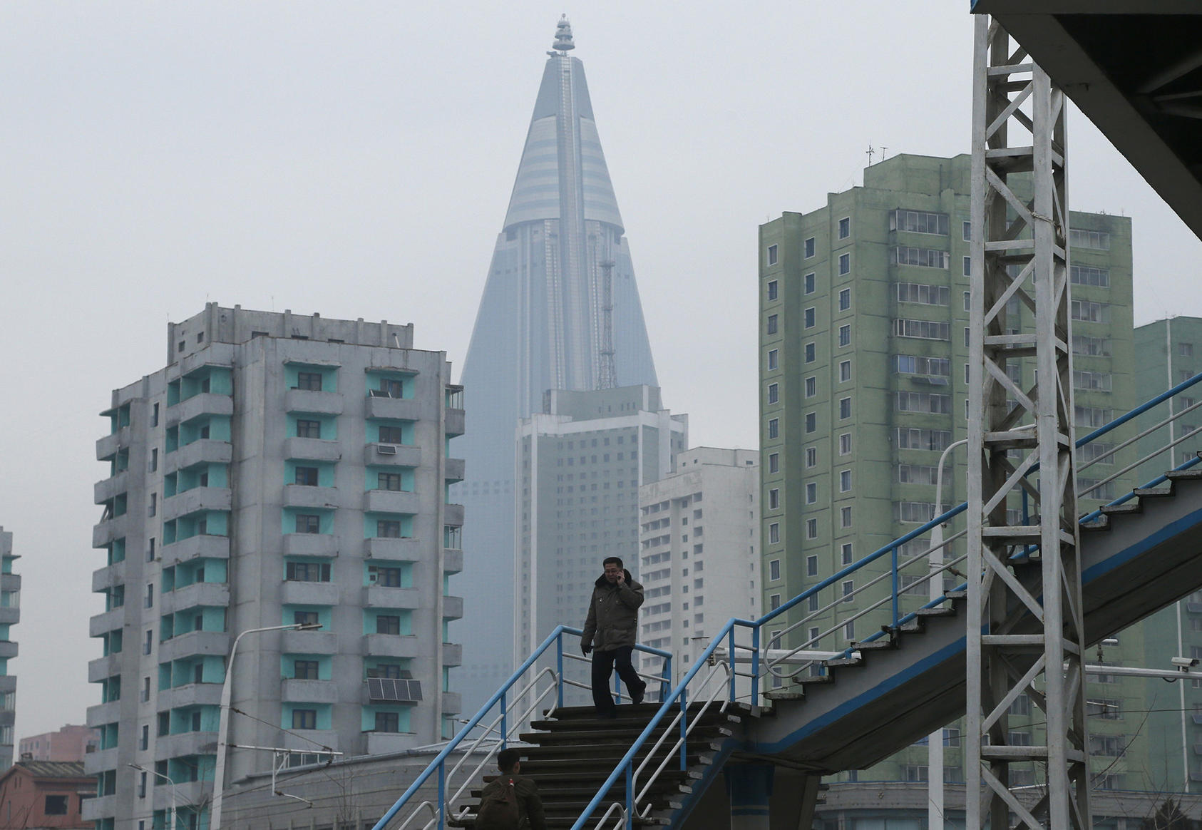 A man talks on his mobile phone while walking in downtown Pyongyang on December 15, 2018. (Photo by Dita Alangkara/AP)