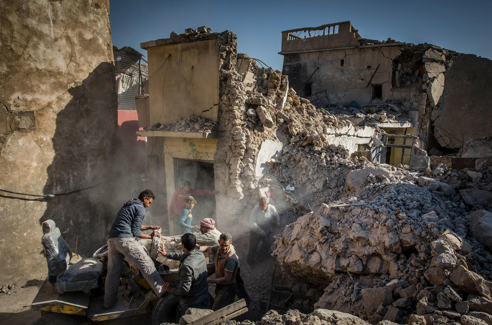 A family begins the arduous task of rebuilding its destroyed home in the heavily damaged Old City in west Mosul, Iraq, Dec. 4, 2017. (Ivor Prickett/The New York Times)