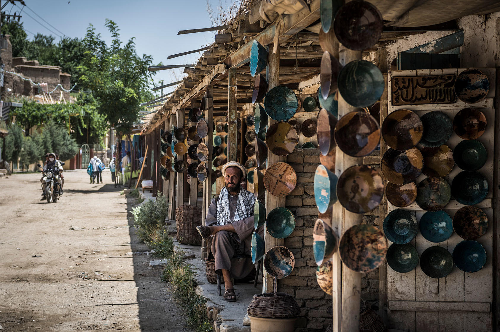 Shops on the main street through Istalif, Afghanistan, where they make distinctive turquoise pottery, June 30, 2016. (Sergey Ponomarev/The New York Times)
