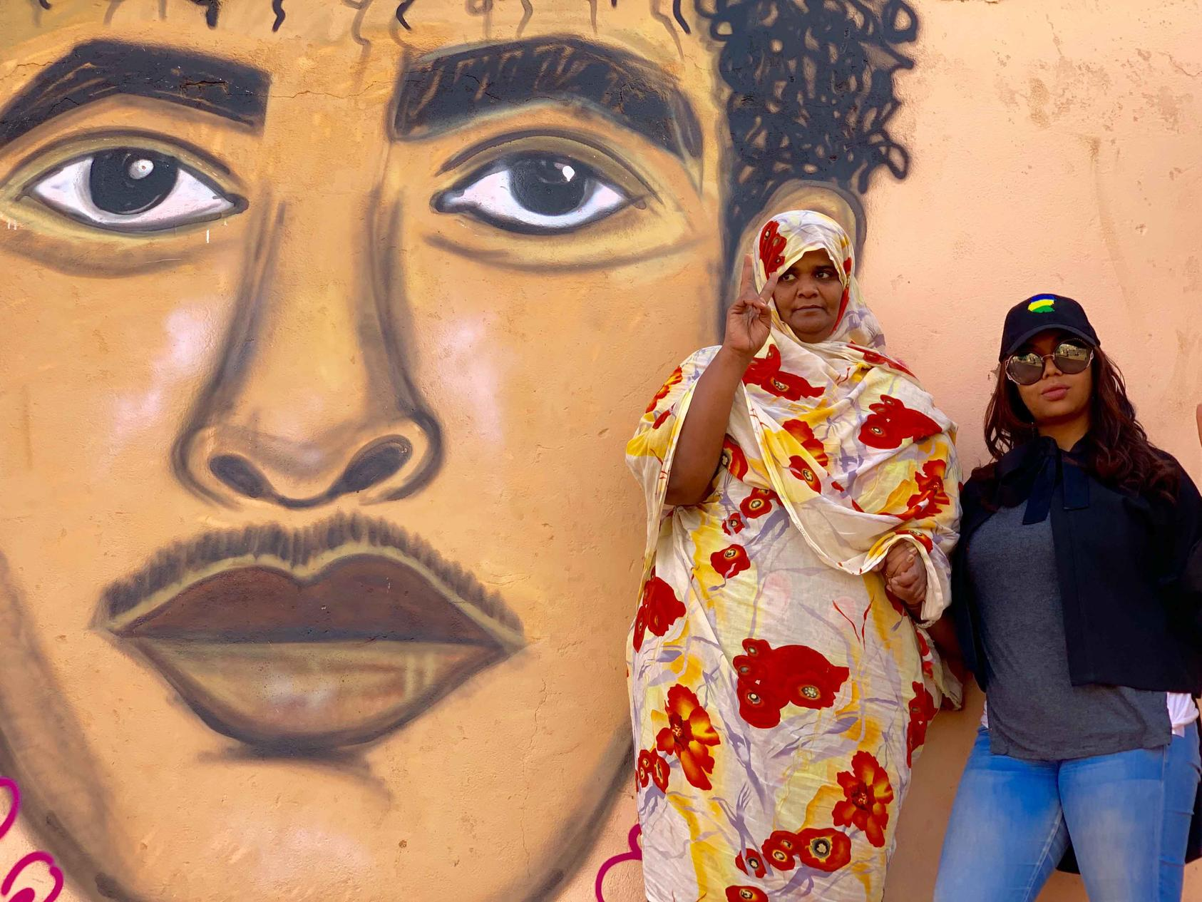 Assil Diab poses with Ahlam Khidr, protest leader and activist, in front of Assil's mural of Ahlam's son Hazaa Izzeldine Jaafar, who was killed while peacefully protesting Bashir's regime in September 2013.