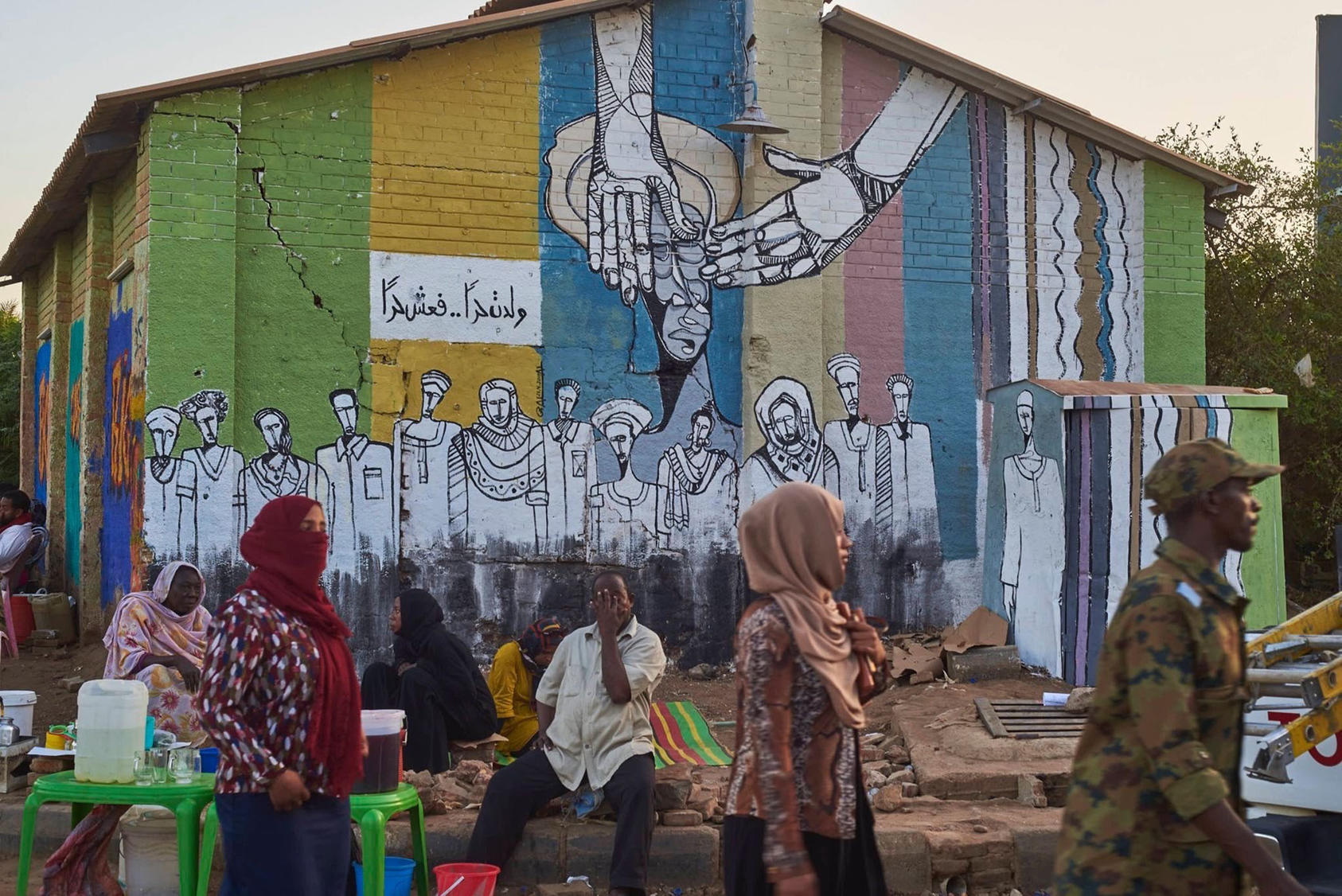 "A mural by Galal Yousif near the sit-in site reads ""you were born free, so live free."" (Sari Ahmed Awad)"