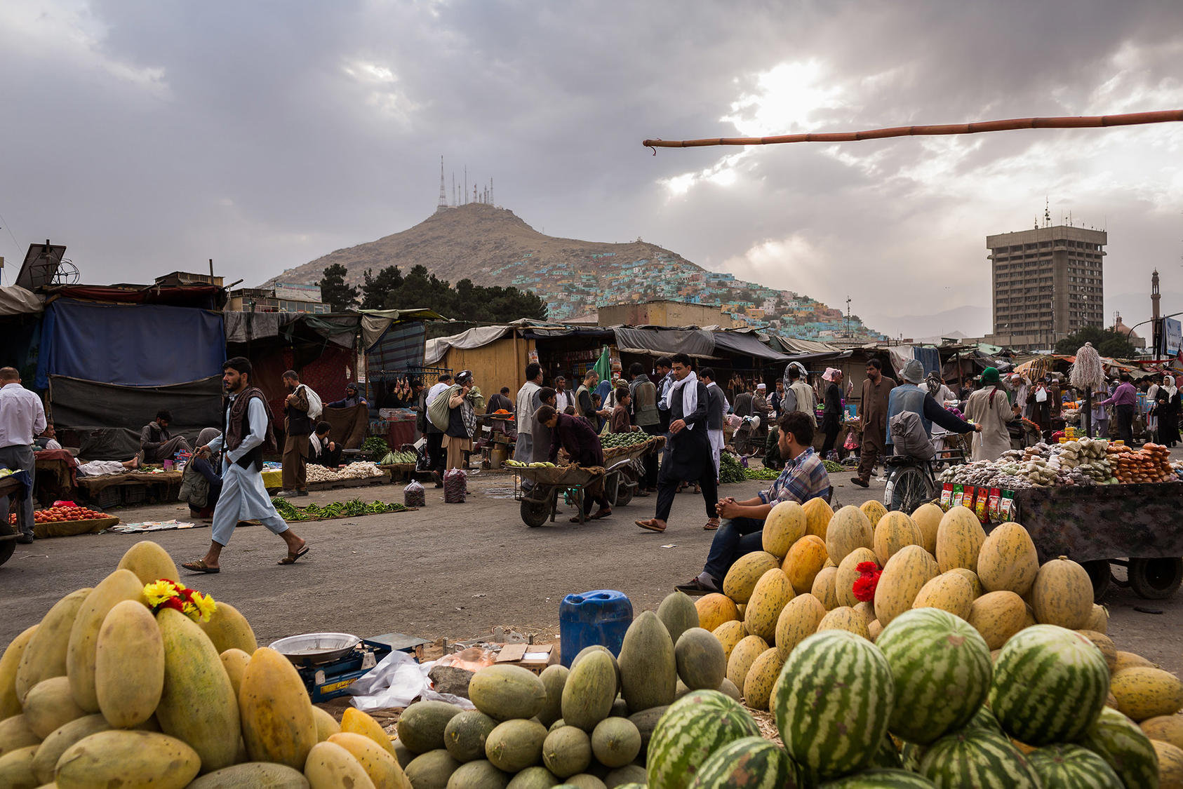 Customers shop for fruits at the retail market along Kabul river in Afghanistan in 2017. (Jim Huylebroek/The New York Times)