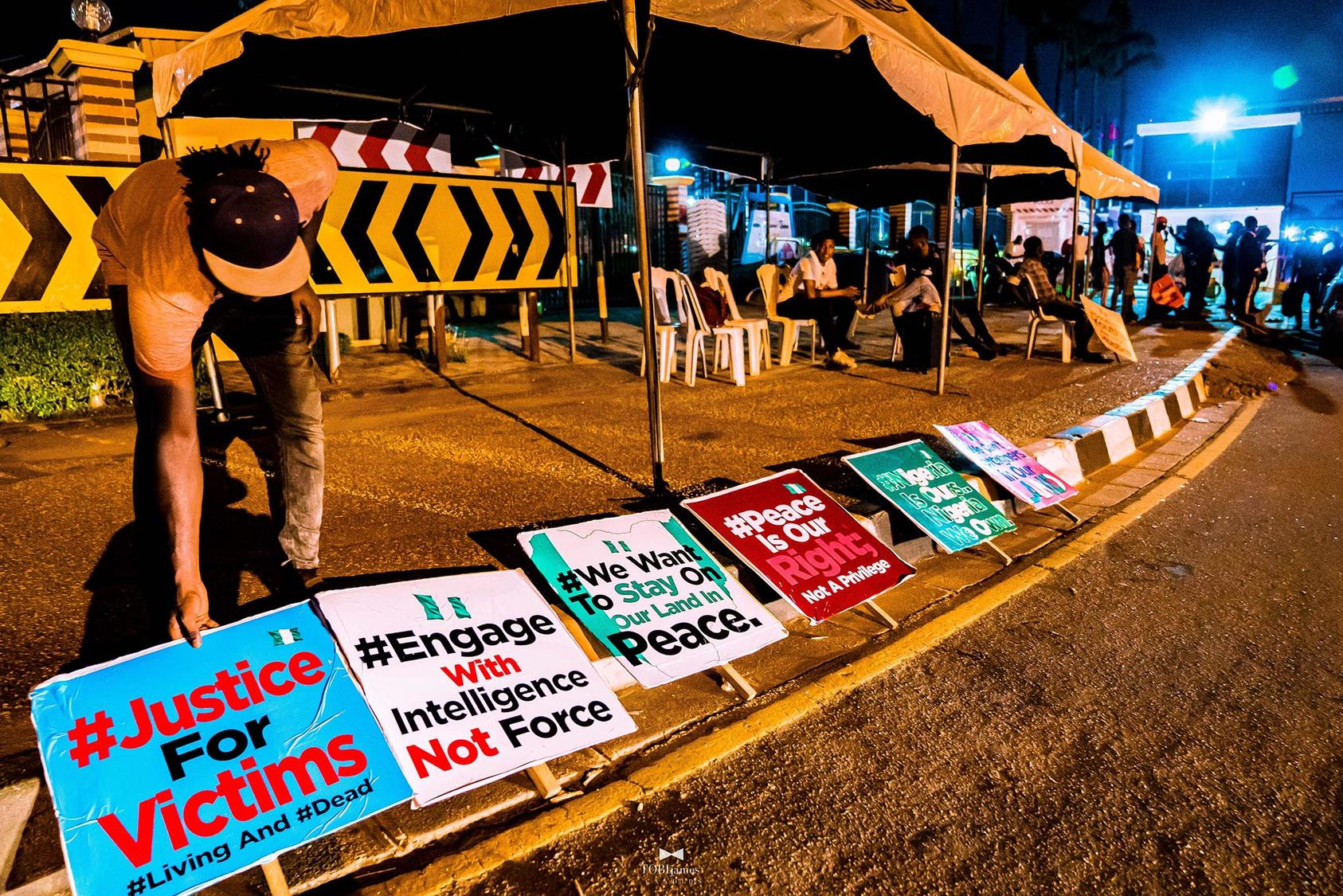 A protester spreads various placards that convey messages against the unlawful killings carried out by SARS, October 8, 2020. (TobiJamesCandids/CC License 4.0)