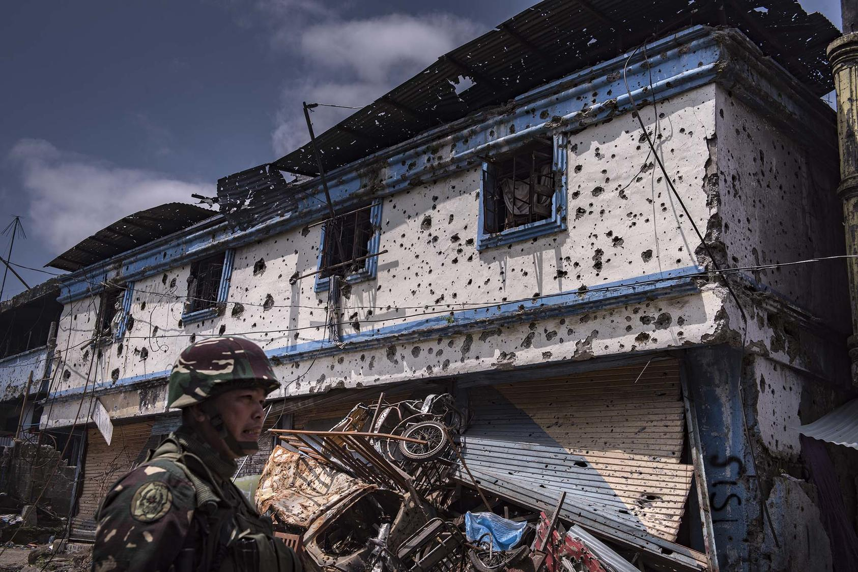 A government soldier outside a ruined building in Marawi, a city in the southern Philippines that was for months under the control of an affiliate of the Islamic State group, Aug. 30, 2017. (Jes Aznar/The New York Times)