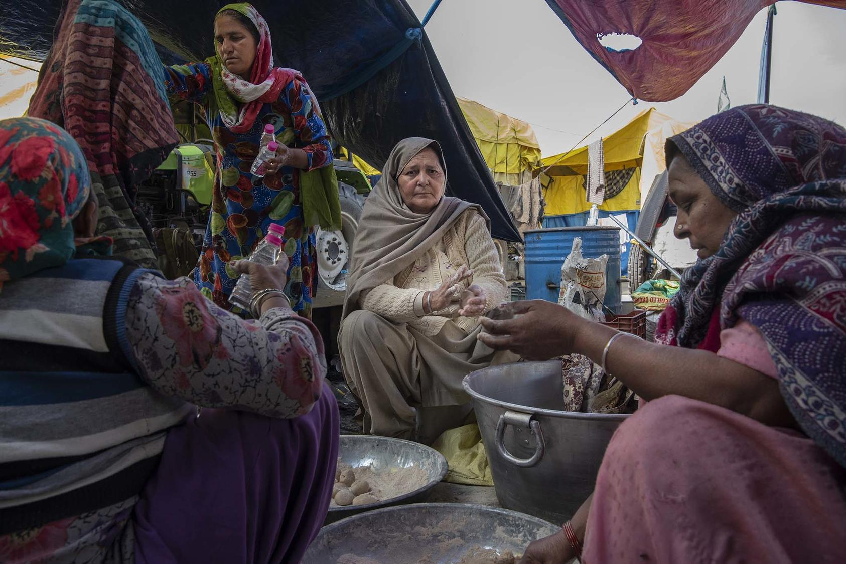 Gurmeet Kaur, center, preparing chapati, in Singhu, India, Jan. 4, 2021. Protesters have created camps around Delhi that are virtual cities unto themselves, using own organizational skills to protest new government farm policies. (Saumya Khandelwal/The New York Times)