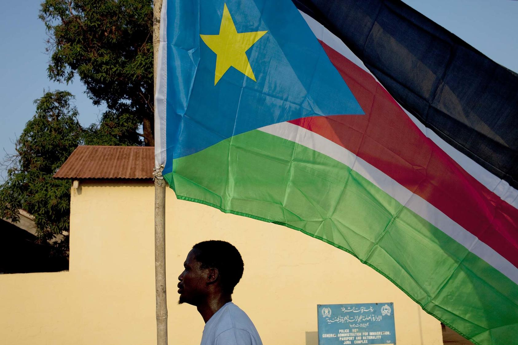 A man carries a southern Sudan flag through the town of Juba, southern Sudan, July 8, 2011. (Tyler Hicks/The New York Times)
