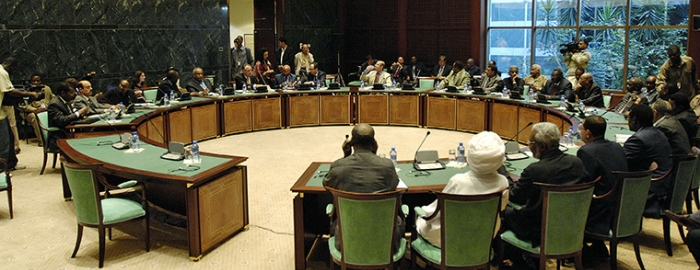 Wide-view of a closed door meeting between the African Union and the United Nations (AU/UN) mediation team (left side of table), and the delegation of the Government of Sudan (right side of table) in Sirte, Libyan Arab Jamahiriya.