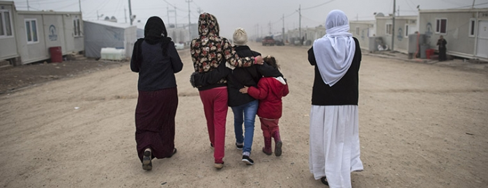 """""""M."""", center, a Yazidi teen who escaped sex slavery under the Islamic State group, is comforted by relatives before leaving to be resettled in Germany, at a camp near Dohuk, Iraq, Jan. 24, 2016. Islamic State leaders have made sexual slavery integral to the group's operations, aggressively pushing birth control on the victims to keep the trade running. (Lynsey Addario/The New York Times)"""