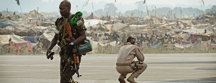 An African Union soldier and U.S. airman share the tarmac of the Central African Republic's main airport as refugees from the CAR's war watch peacekeepers' arrival in 2014. Photo courtesy of DIMOC/SSgt Ryan Crane