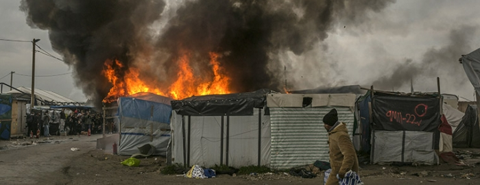 A refugee carries his belongings amid dwellings burning at a makeshift camp where 6,000 or more have been living in Calais, France. Several dwellings were set on fire by migrants to protest eviction. Photo Courtesy of The New York Times/Mauricio Lima