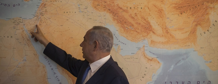 Prime Minister Benjamin Netanyahu by the floor-to-ceiling map with Israel at its center, at in his office in Jerusalem, July 1, 2016. Netanyahu is fond of staring at the map, and regaling visitors with stories about how Israel has made friends with so many of the countries shown, some nearby, others far away.