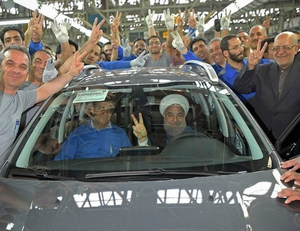 Rouhani in a car fresh off the line in a factory