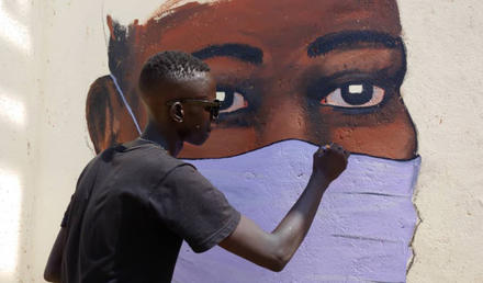 An artist paints one of many murals that civic activists use to win public support for efforts to halt COVID. (Anataban)