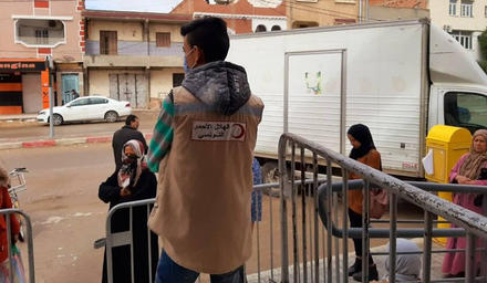 A volunteer with the Tunisian Red Crescent organization facilitates the disbursement of financial assistance in Gafsa, Tunisia. (Tunisian Red Crescent)