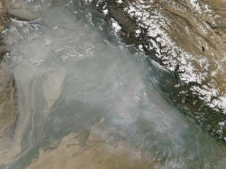 Below the snowcapped Himalayan range, a gray haze blankets Pakistan and northwest India in October 2010. To the right of the faint, gray border line, red dots show fires set to clear stubble from Indian farmlands. (NASA satellite photo)
