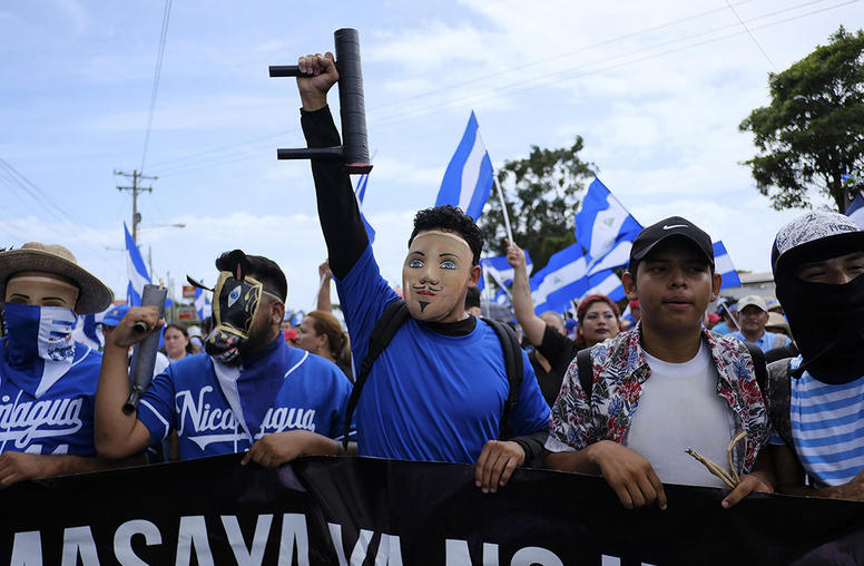 Protesters wearing folkloric masks and carrying crude, homemade mortars march through Managua, Nicaragua, July 12, 2018