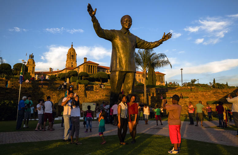 People visit a statue of former South African President Nelson Mandela in Pretoria, South Africa. (Daniel Berehulak/The New York Times)